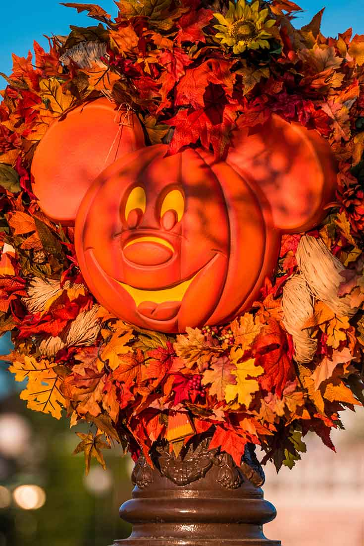 Closeup of some Fall and Halloween decorations at Disney World's Magic Kingdom, with a wreath made of Fall leaves and sunflowers and a pumpkin shaped Mickey Mouse Head in the middle.