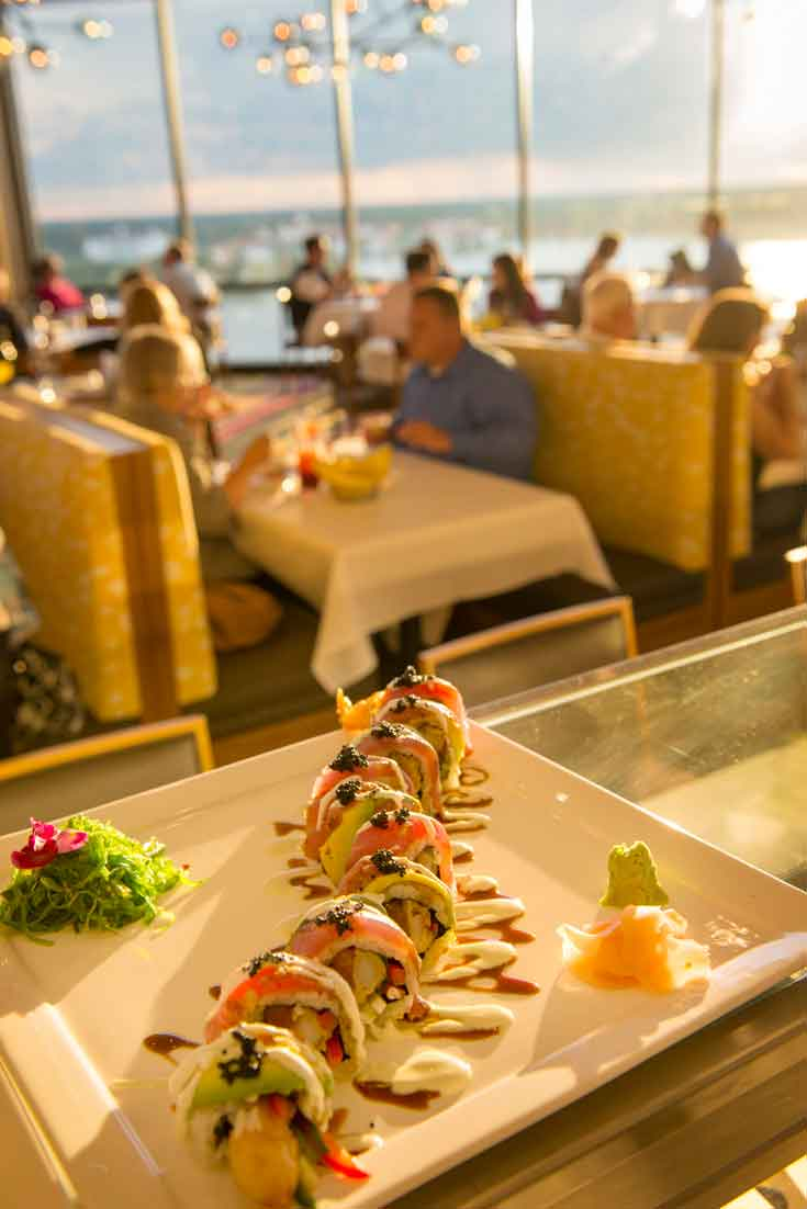 Close up photo of a special sushi roll with diners in the background at California Grill.