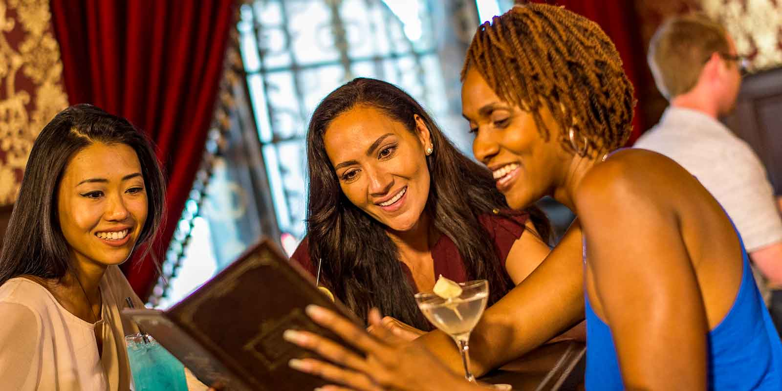 Three women peruse a drink menu at Disney Boardwalk's AbracadaBar.