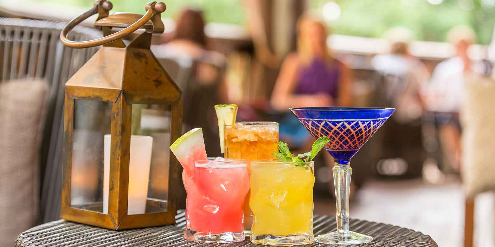 Closeup of 4 brightly colored cocktails on a lounge table at Animal Kingdom's Nomad Lounge.