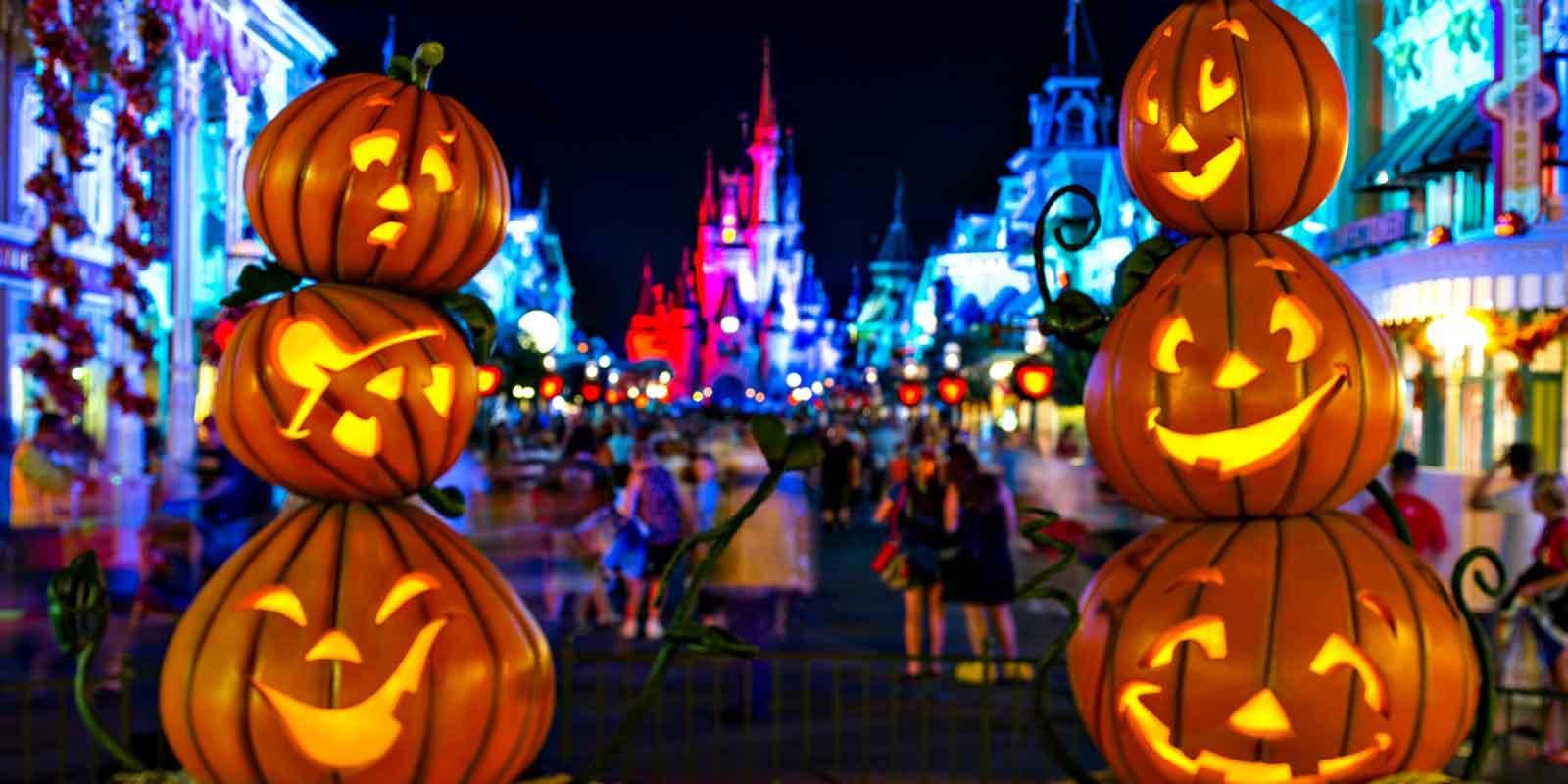 Closeup of 2 vertical stacks of pumpkins framing Cinderella's castle at Magic Kingdom.