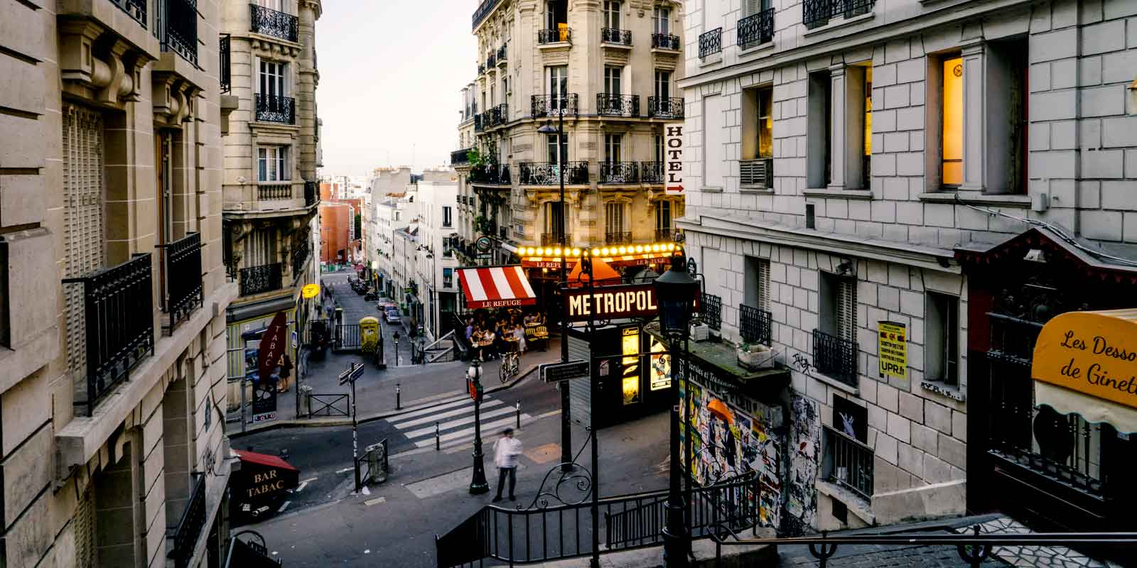 Landscape view of a Parisian neighborhood, with a Metro station, in the background.