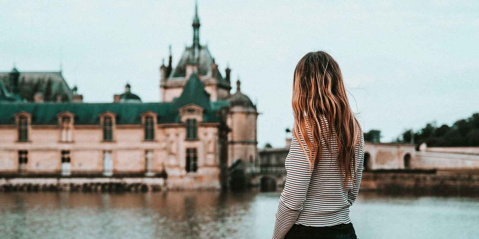 Landscape view of a woman looking at the Château de Chantilly in the background.