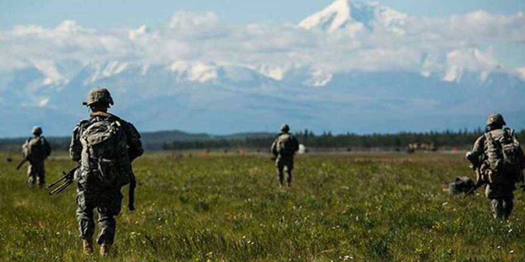 A group of US Army soldiers practice in a green field overlooking a mountain range.