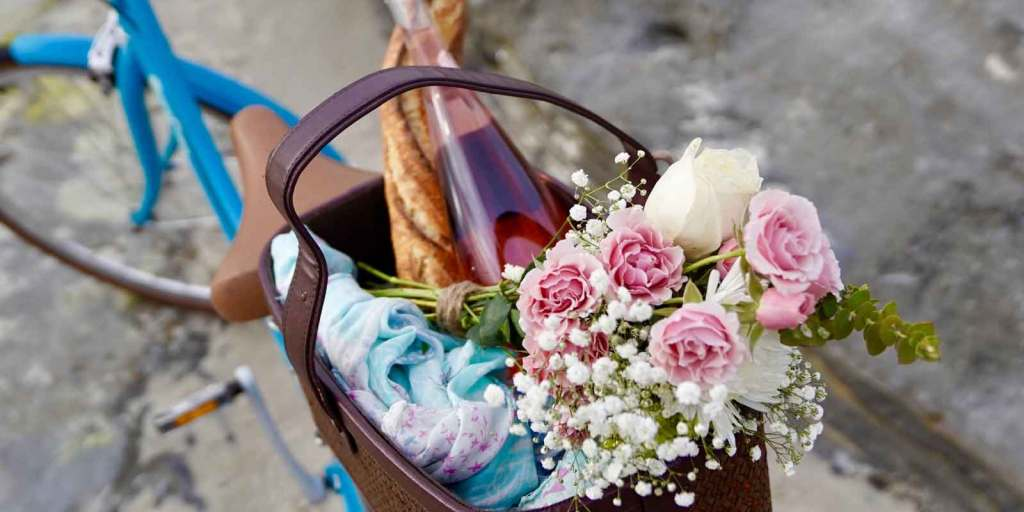 Close up of a basket on the back of a blue bicycle, filled with a baguette, bottle of pink wine, a blue and pink blanket or scarf, and a bouquet of pink carnations, white roses, and greenery.