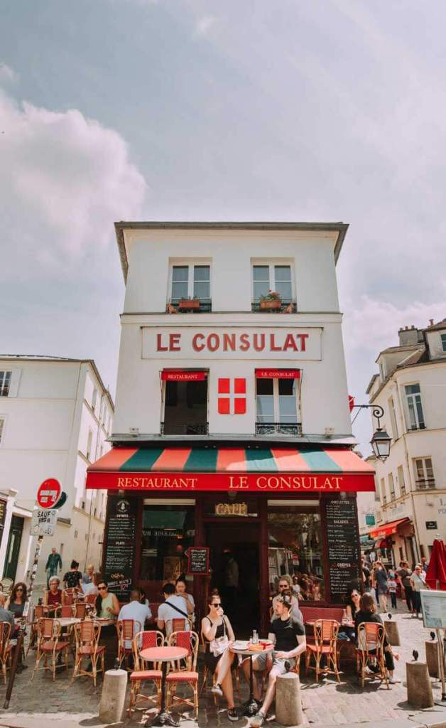 Photograph of Le Consulat restaurant in Paris, France, with people dining outside on a clear day.