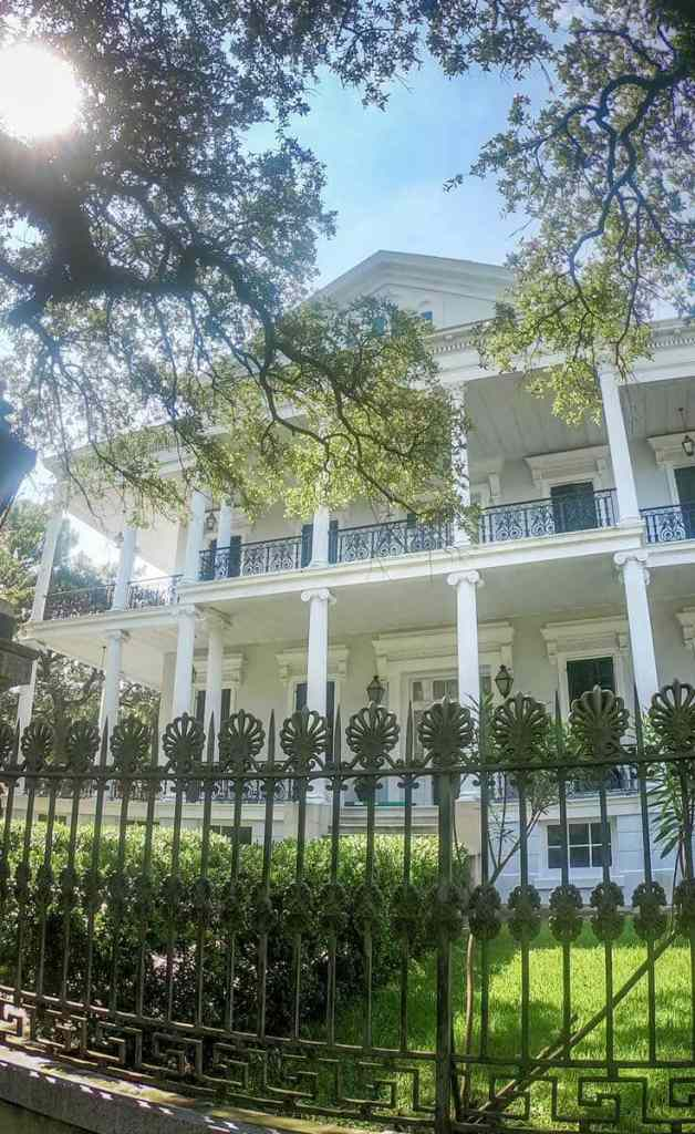 Close up of a white Southern mansion, known as the Buckner Mansion, in New Orleans' Garden District.