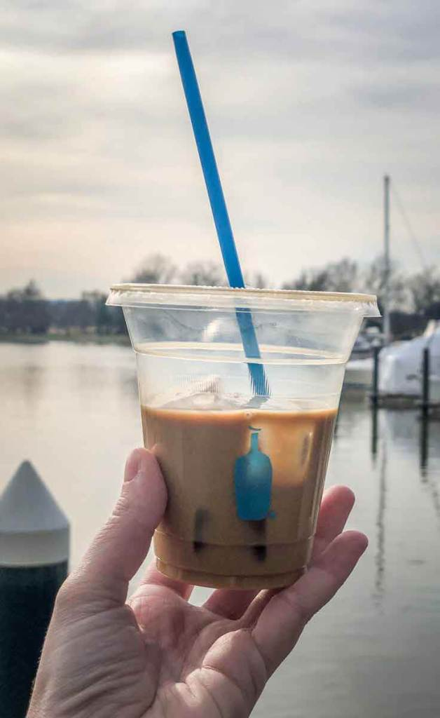 Closeup of a half empty New Orleans style iced coffee from Blue Bottle Coffee in front of a marina in DC.