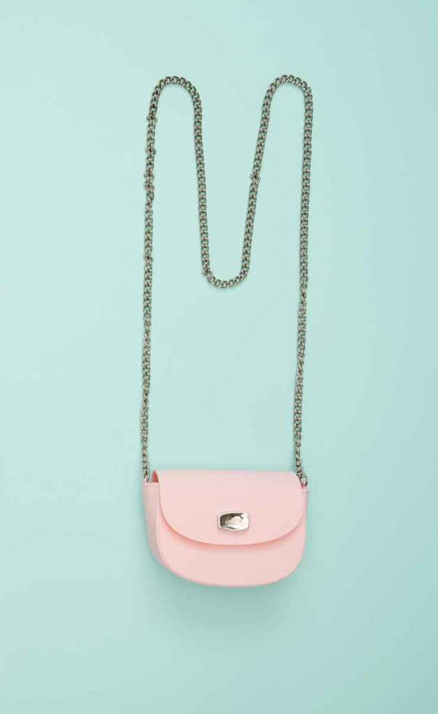 Photograph of a pink crossbody bag on a mint green background.