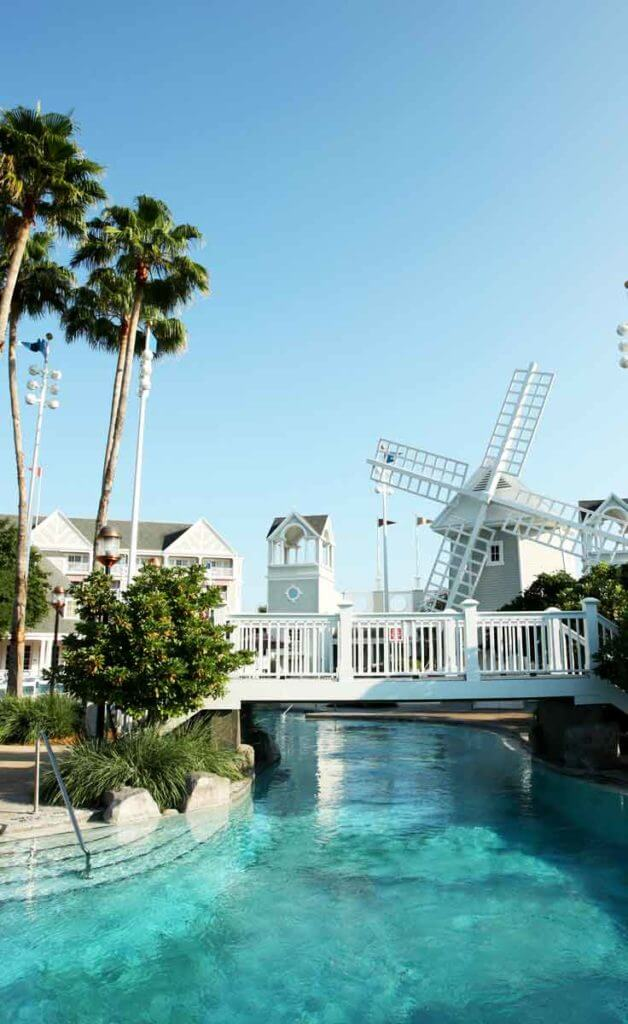 Photograph of a section of the Stormalong Bay pool at Disney World, featuring a white bridge, turquoise water, a windmill, and part of a resort building in the background.
