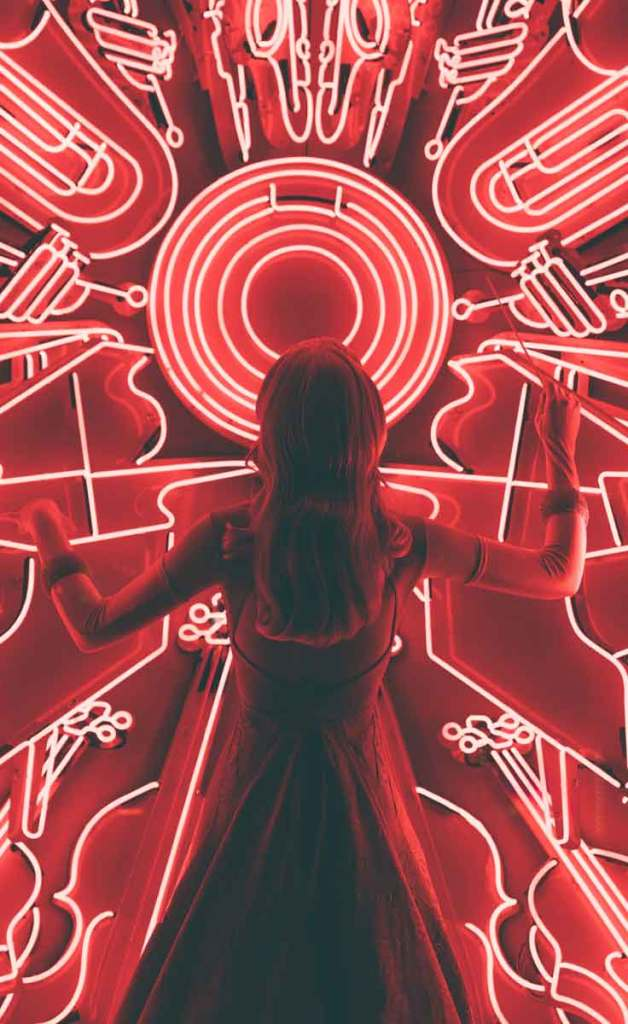 Woman in a dress examines a red neon sign that features Jazz instruments, like a piano and trumpet.