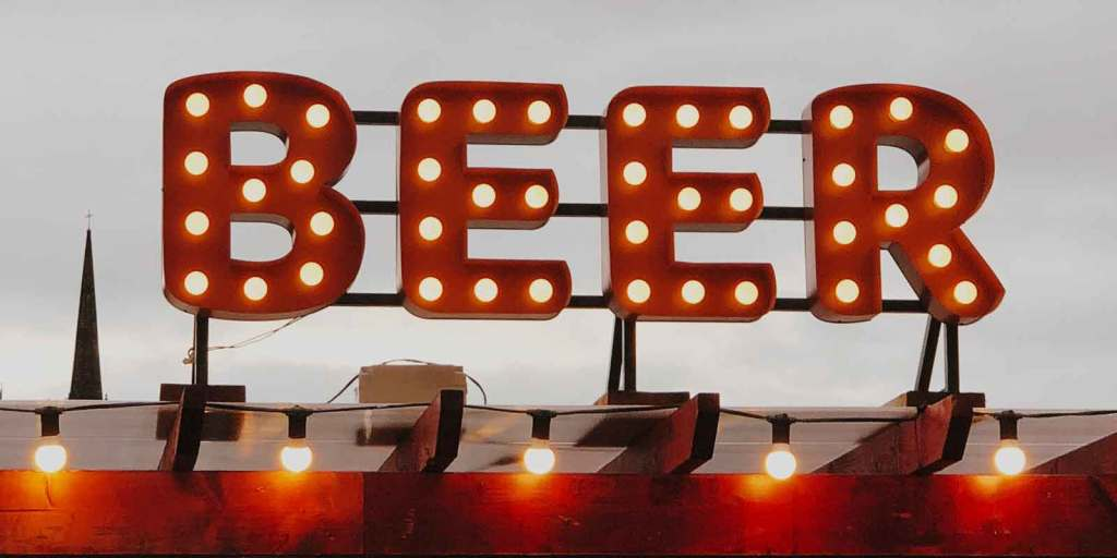 Close up of a large sign with red letters and lightbulbs spelling out BEER.