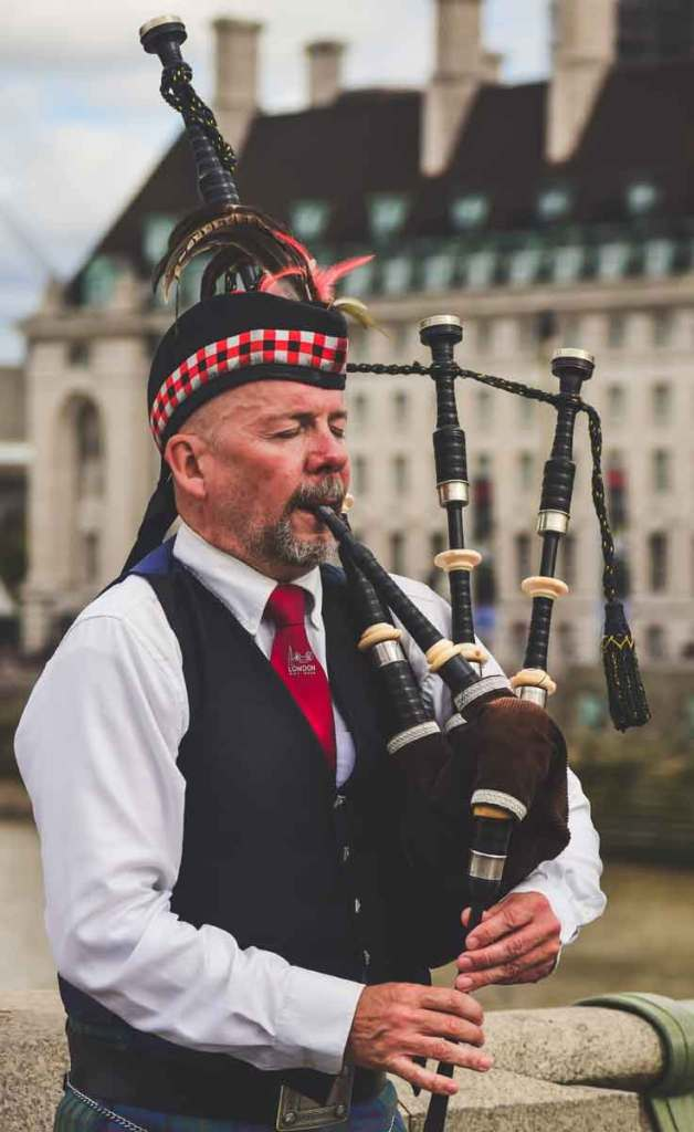Closeup of a man wearing a kilt uniform, playing bagpipes.