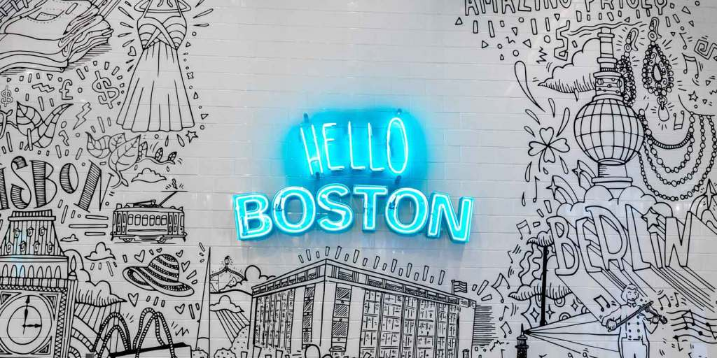 """Black and white drawing on subway tile with a blue neon sign in the middle that reads """"Hello Boston."""""""