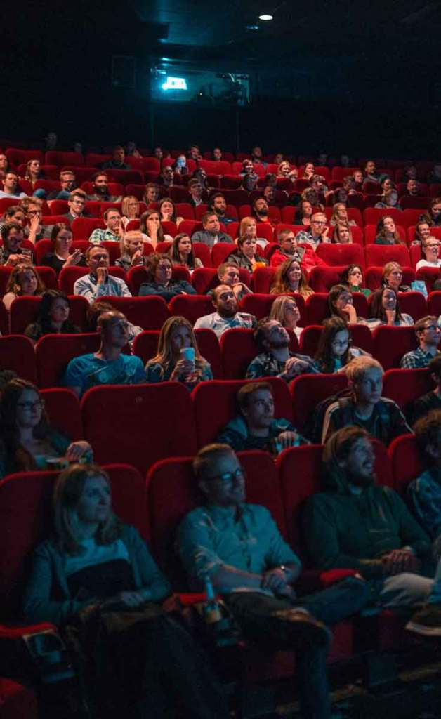 A crowd of people sitting in red seats in a darkened movie theater.
