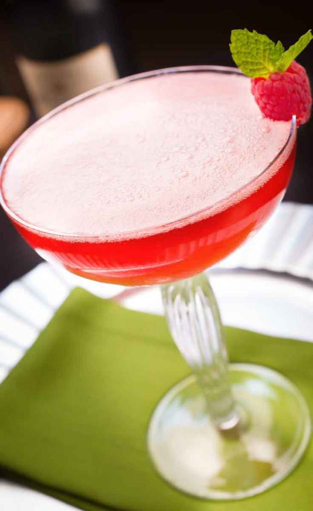 Closeup of cherry pink cocktail with millions of bubbles on the surface in a margarita glass.