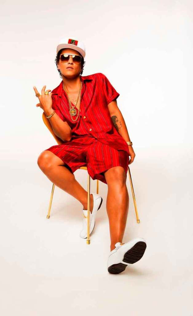 Promo photograph of R&B singer Bruno Mars. Mars is wearing a red silk button up top and shorts with lots of gold jewelry, white loafers, and a white baseball cap.
