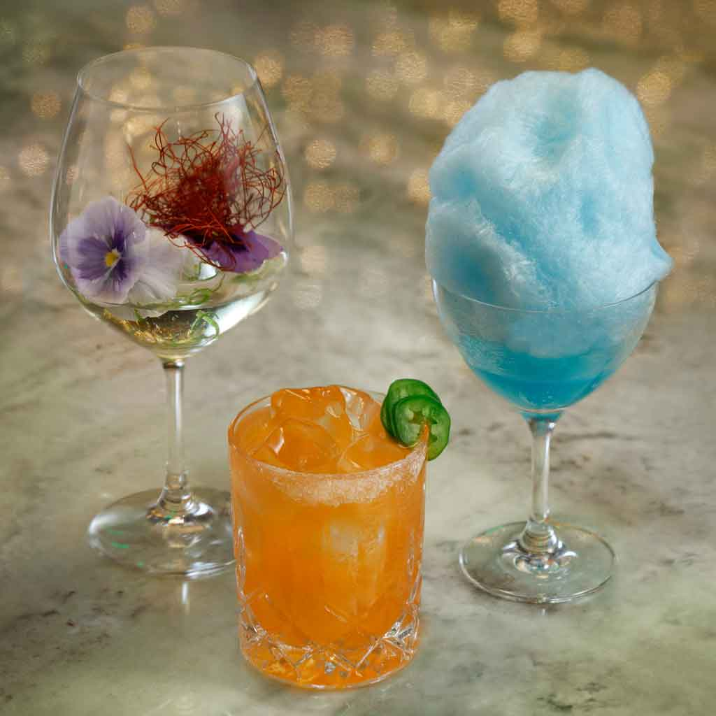 Closeup of 3 cocktails, one in a deep wineglass with a violet garnish, another bright orange cocktail with jalapeño garnish, and the last with a tall puff of baby aqua cotton candy.