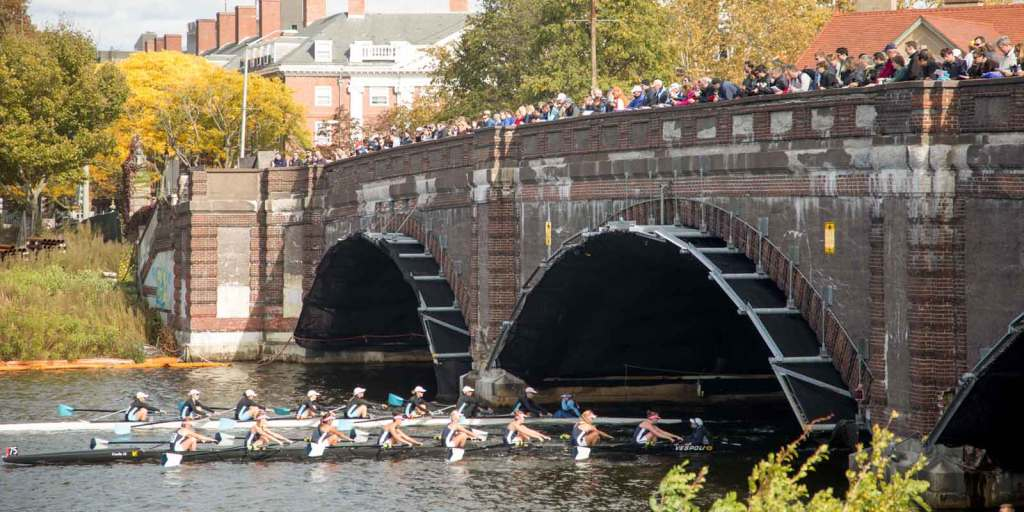 2 8-person rowing boats glide through the Charles River, while crowds watch from a bridge above.