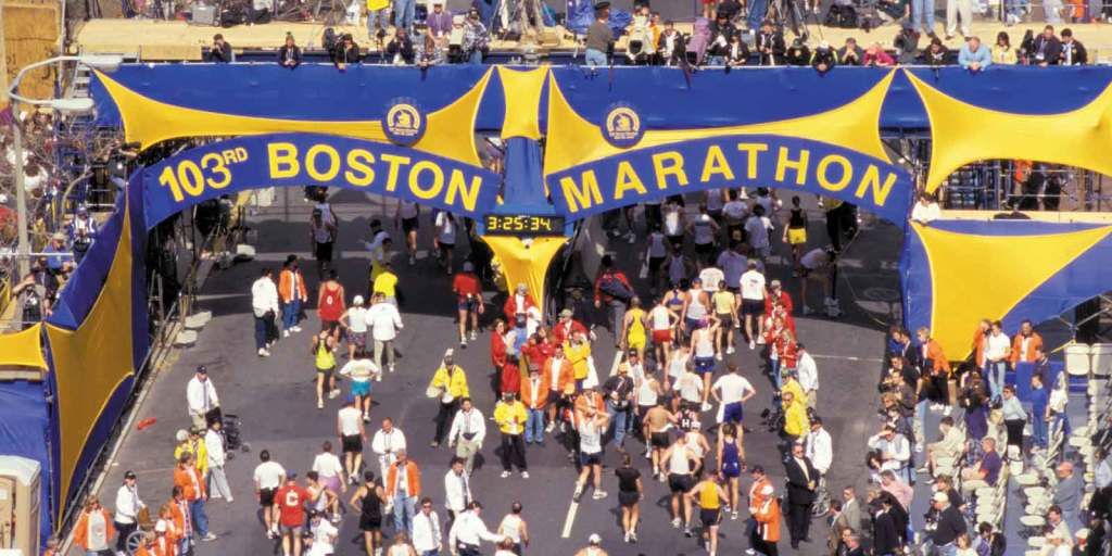 """Landscape view of race route for the Boston Marathon with a blue and yellow sign that reads """"103rd Boston Marathon."""""""