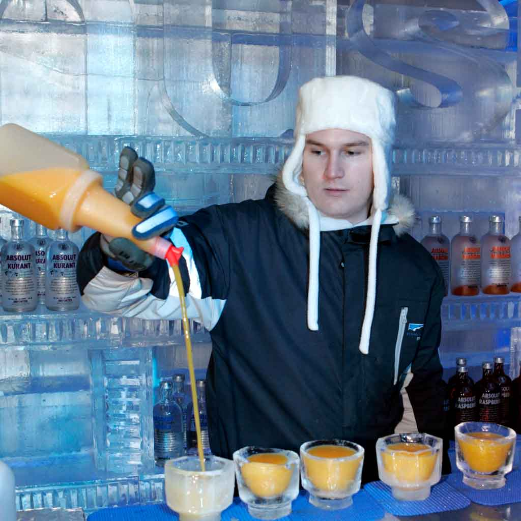 Photograph of a man dressed in Winter gear pouring an orange cocktail at Minus 5 Ice Bar in Las Vegas.