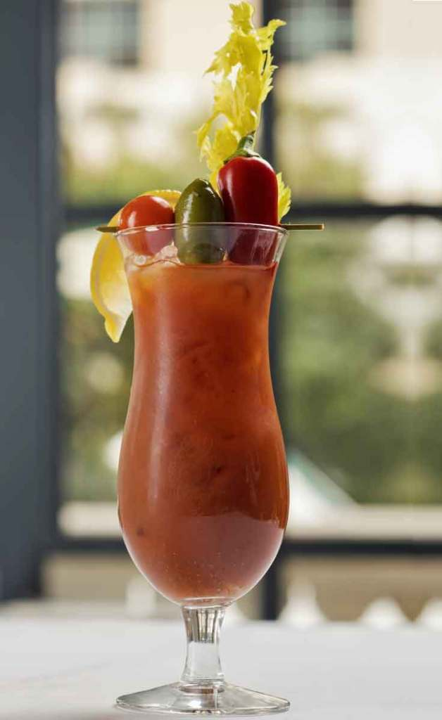 Closeup of a tall hurricane glass with a Bloody Mary cocktail, complete with a lemon wedge, stalk of celery, and a skewer with a tomato, olive, and chile pepper.