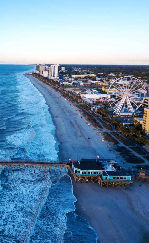 Aerial view of a long stretch of beach with a pier stretching into the ocean, tall resort buildings, and a ferris wheel dotting the shore.