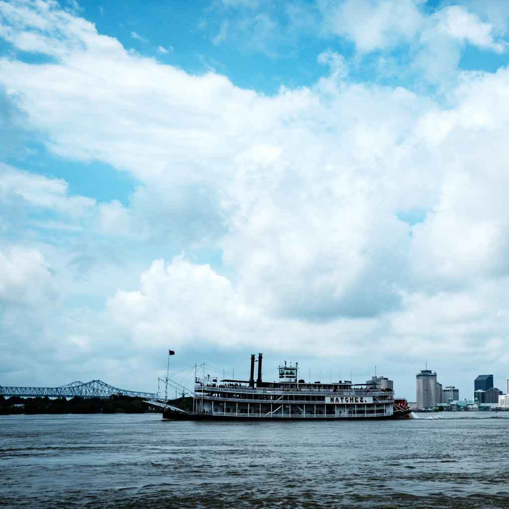 """Photograph of blue, yet cloudy, skies with a steamboat floating by with a sign that says """"Natchez."""""""