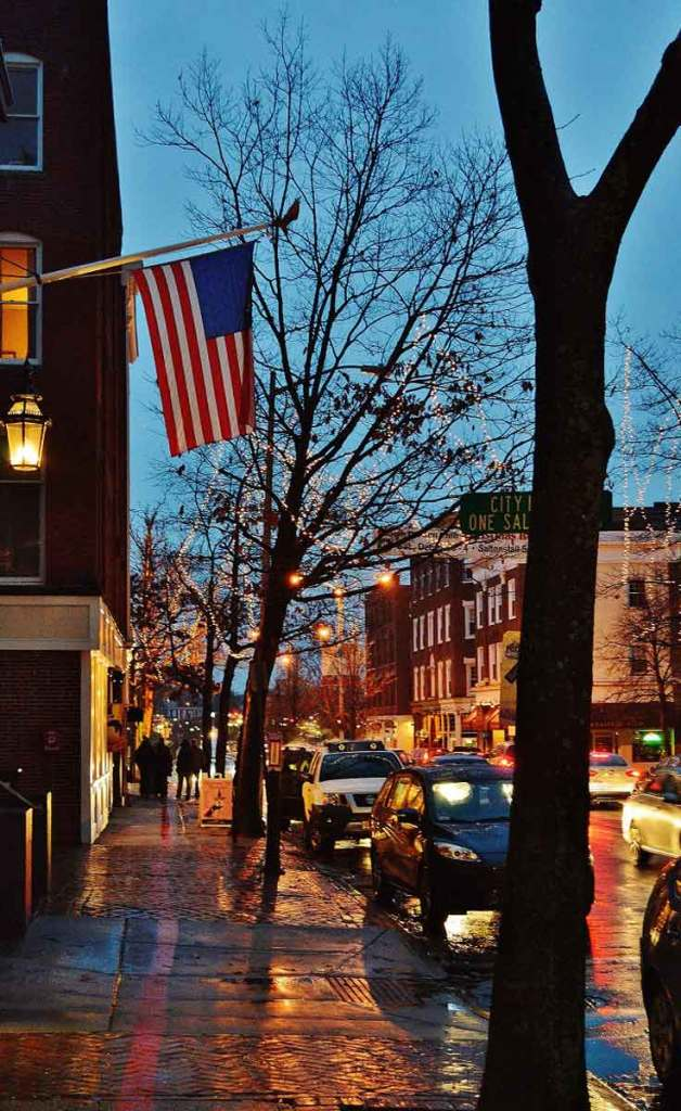 View of Washington Street in Salem, MA during dusk with white lights on bare trees and a American flag hanging from a brick building.