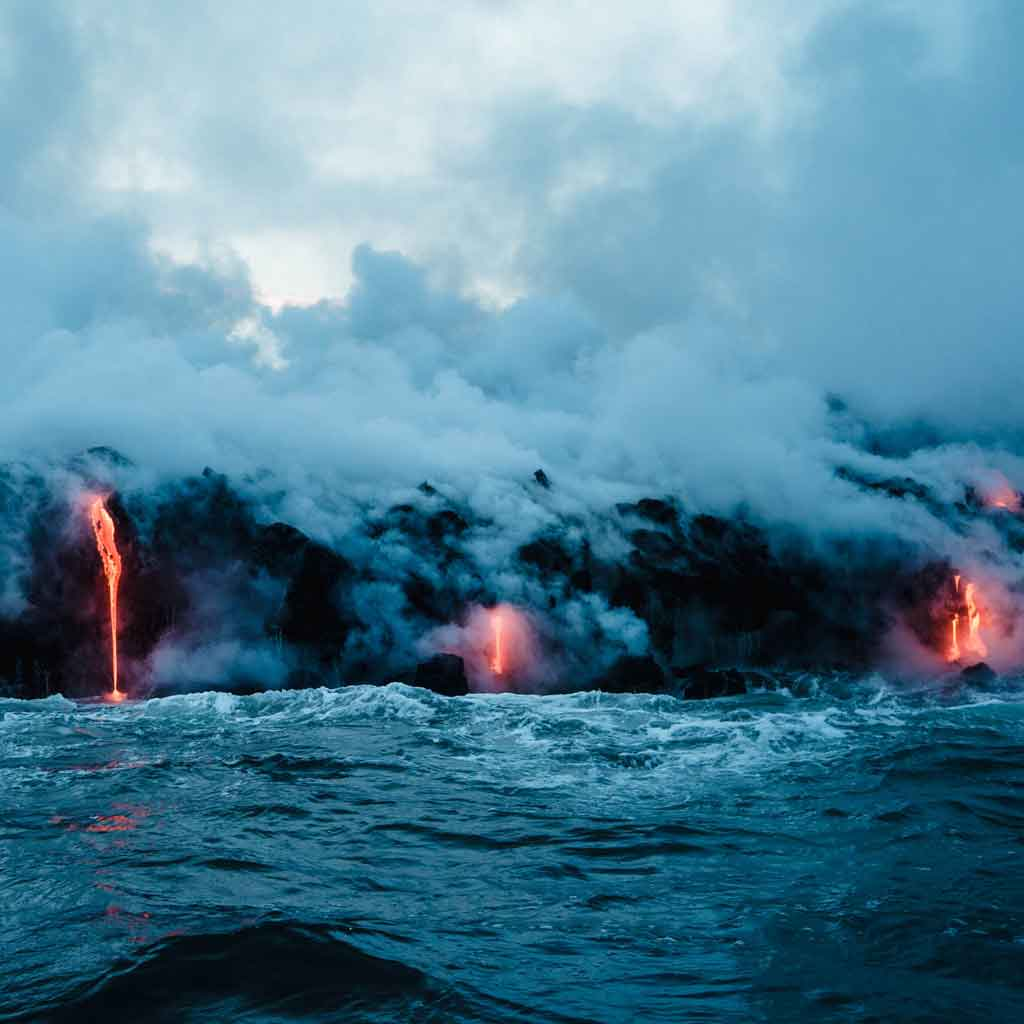 Smoke and hot lava pouring over volcanic rock into the ocean.