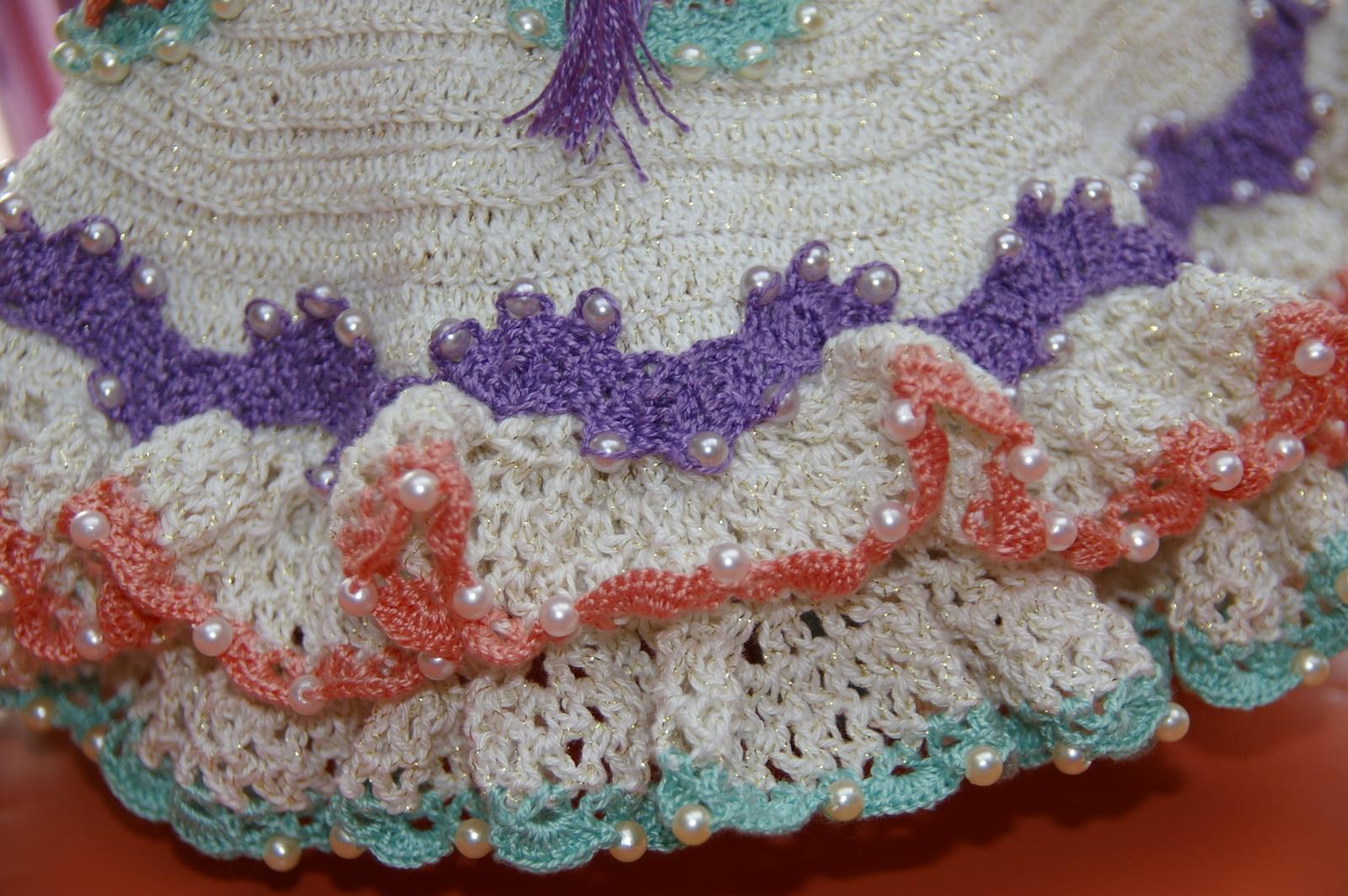 Les volants de la jupe avec des perles et le galon en dentelle de Bruges.
