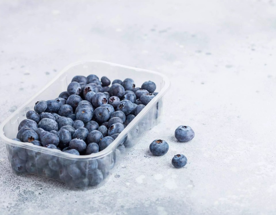 Plastic tray container of fresh organic healthy blueberries on stone kitchen table background. Space for text