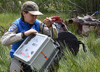 A woman handles a metal box with power cords to set up an electrofishing unit to help catch the fish.