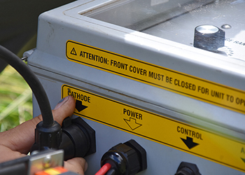 A hand plugs in a power cord into an electrofishing system.
