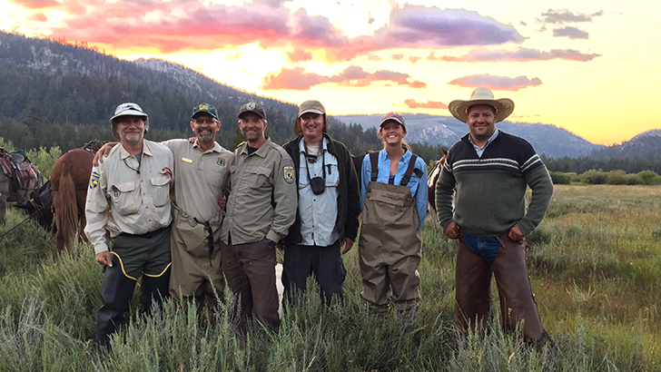 A group of men and women pose for the camera wearing waders in a meadow.
