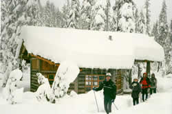 Maiden Peak Shelter with deep snow on roof and skiers along side