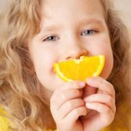 Child with orange slice smile