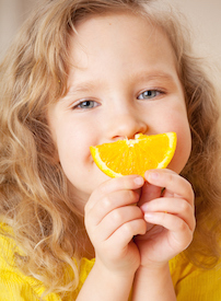 Child with orange slice smile