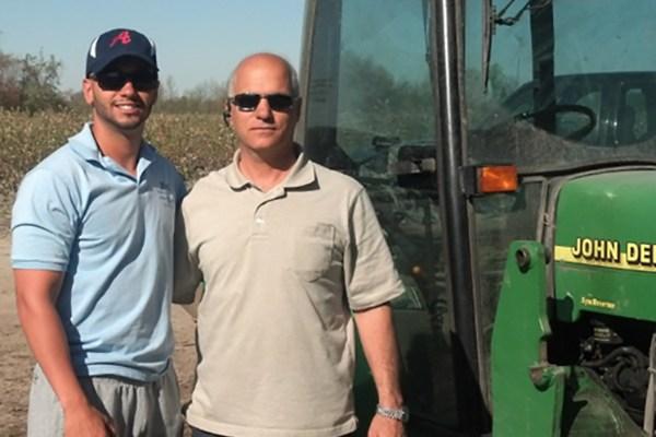 Two men standing on farm