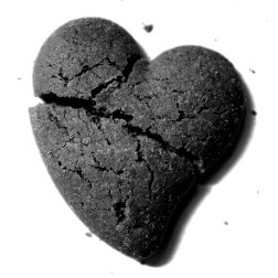 Photo of a black clay heart, cracked upon from side to side.