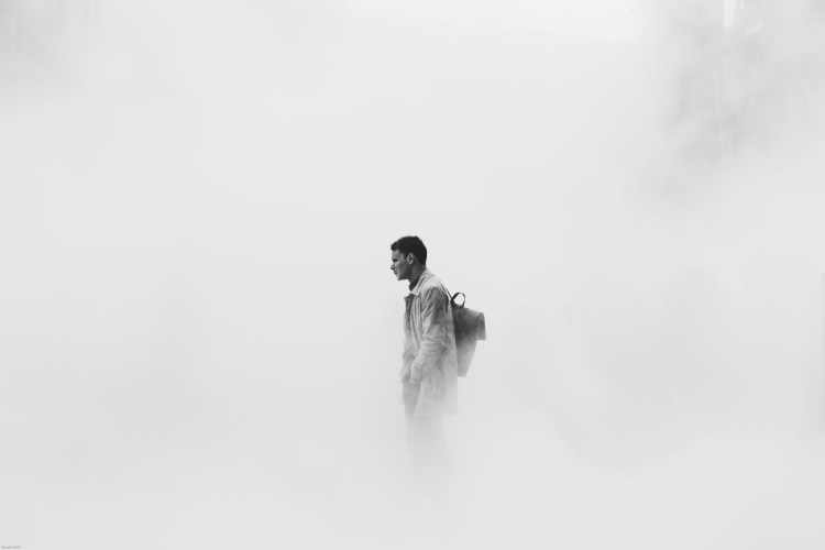 This is a photo of a person standing alone and still in a heavy fog.