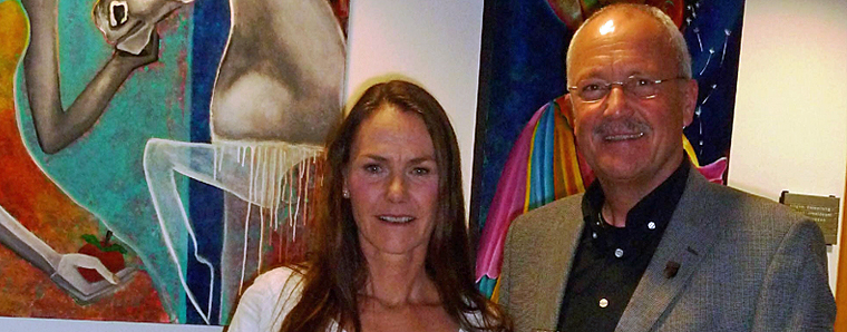 Die Künsterlin Janett Rotter mit Bürgermeister Manfred Helfrich vor zwei ihrer farbenfrohen Werke im Rathaus Poppenhausen.