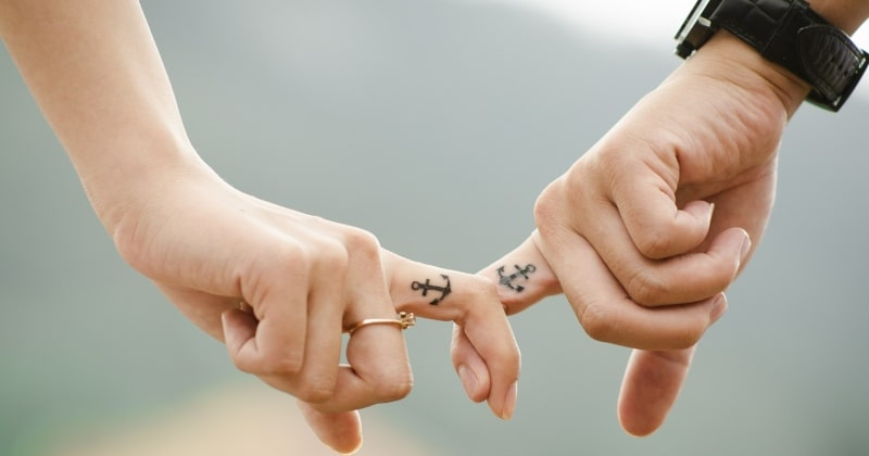 Radiant relationships during parenthood with a couple holding fingers