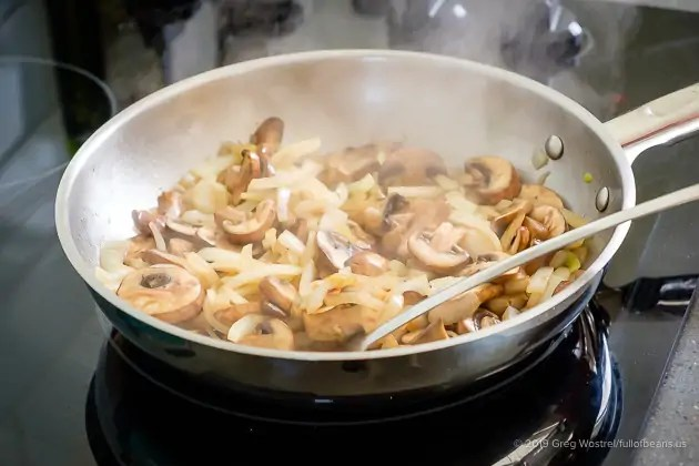 mushrooms and onions cooking in a pan
