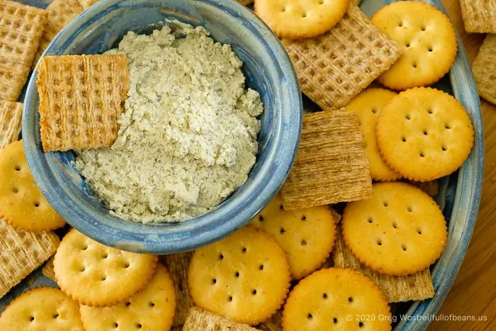 bowl of soft herb cheese surrounded by crackers