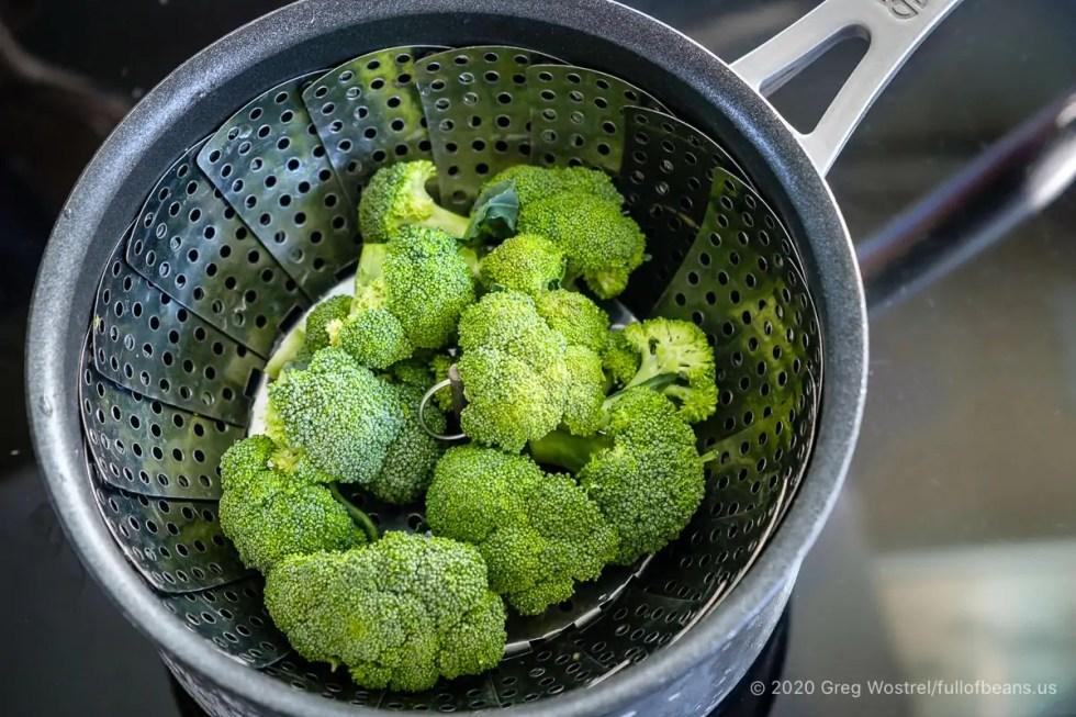 raw broccoli in a stainless steel veggie steamer basket