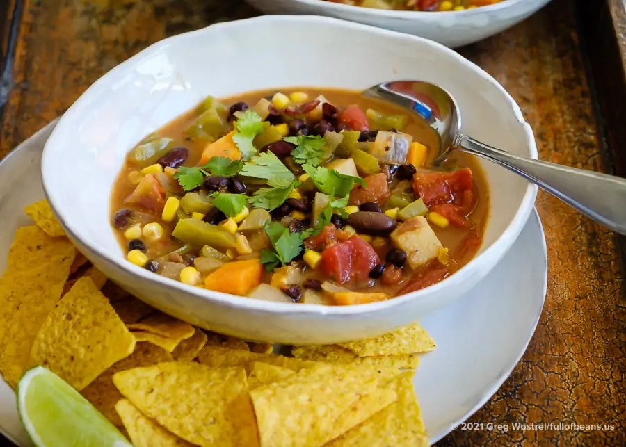 A bowl of Vegan Mexican Soup on a plate with corn chips and a lime wedge