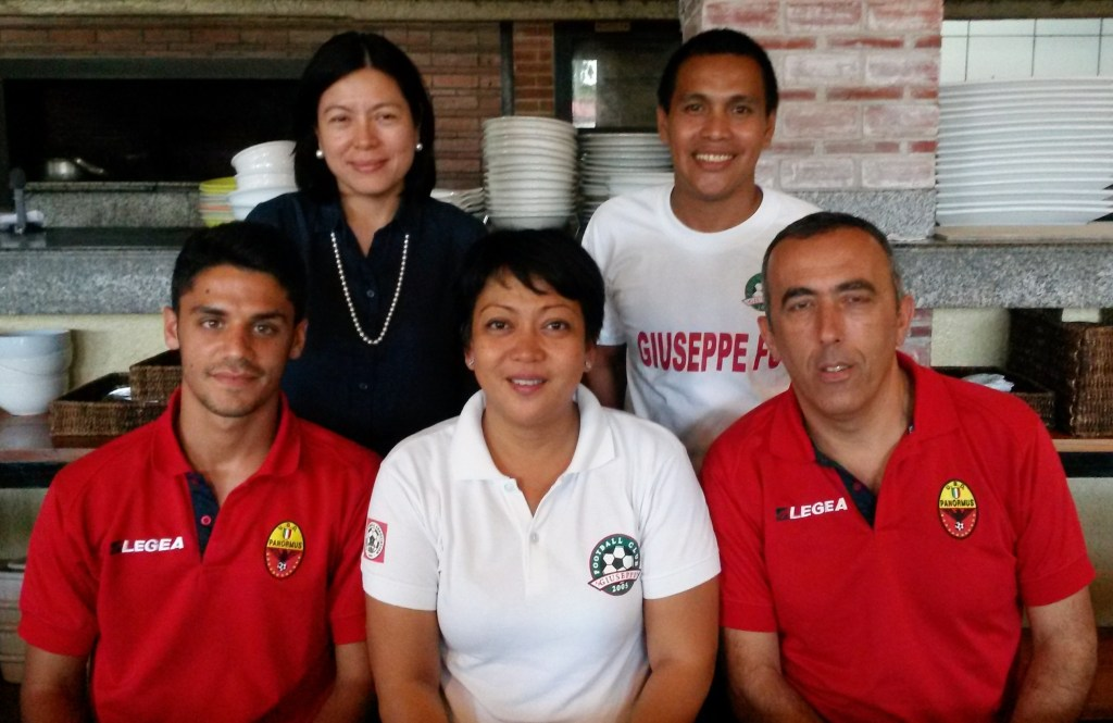 "Giuseppe Football Club owners Mylene Suarez (standing, left) and Rachel Genco (sitting, center) pose with Italian coaches Marco Cumbo (sitting, left) and Nicolo Ferrante (sitting, right). They are joined by GFC coach Oliver ""Bingbing"" Colina (standing, right)."