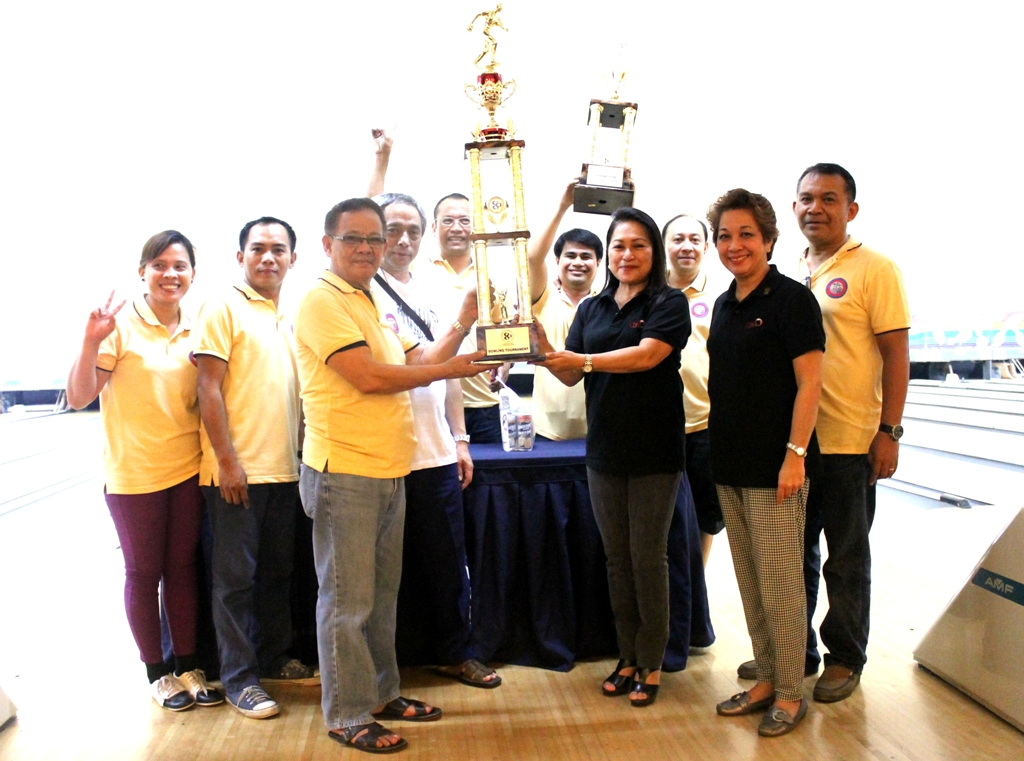 Tess Chan, president of the Cebu Chamber of Commerce and Industry presents the championship trophy of the 2014 CCCI Bowling Tournament to OPASCOR team A at the SM City Cebu Bowling Lanes.