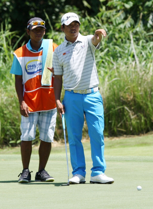 Jay Bayron checks the line of his putt with his caddie on No. 18.